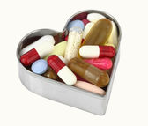 Pills in a heart shaped box — Stock Photo