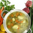 Fresh vegetable soup in a pot with mixed vegetables around it — Stock Photo