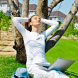 Stock Photo: Pretty female sitting under a tree with laptop on summer day