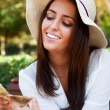 Portrait of young pretty woman sitting on bench at summer or aut — Stock Photo