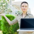 Young businesswoman (real estate agent) holding a laptop and presenting detached family house — Stock Photo #10084750