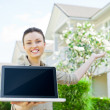 Stock Photo: Young pretty female realty agent with laptop presenting beautiful detached house