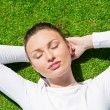 Young beautiful woman on the grass with closed eyes — Stock Photo