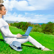 Pretty woman sitting by tree with laptop computer — Stock Photo #10085295