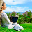 Young woman sitting under tree with laptop and dreaming. Idyllic outdoor scenery - Stock Photo
