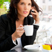 Portrait of pretty young business woman sitting relaxed at outdoor cafe — Stock Photo