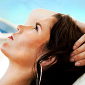 Pretty young woman lying on beach at modern resort. Hotel buildi — Stock Photo