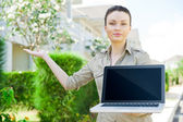 Young businesswoman (real estate agent) holding a laptop and presenting detached family house — Stock Photo