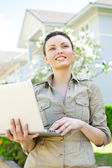 Young pretty female realty agent with laptop presenting beautiful detached house — Stock Photo