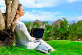 Young woman sitting under tree with laptop and dreaming. Idyllic outdoor scenery — Stock Photo