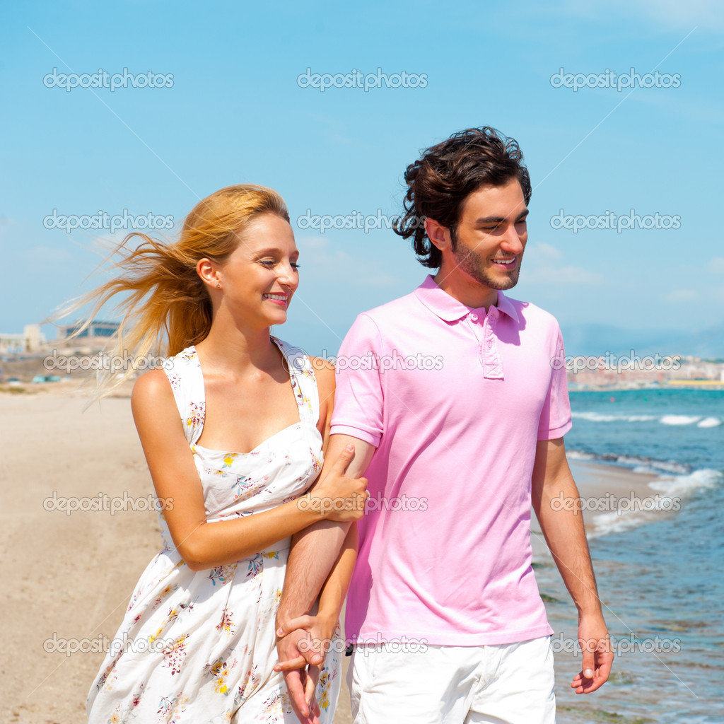 Couple At The Beach Holding Hands And Walking. Sunny Day