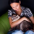 Happy young woman with cat, relaxed on the beanbag couch. — Stock Photo
