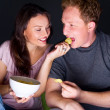 Happy couple sitting together watching something interesting on television and eating - Grey background — Stock Photo