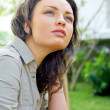Portrait of sweet young woman sitting outdoors at backyard of her house and smiling — Stock Photo #10344556