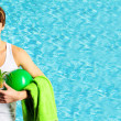 Young handsome man holding ball and towel standing against water pool - Stock Photo
