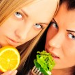 Two beautiful slender girls eating healthy food — Stock Photo #10345065