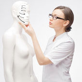 Young female medical doctor student training with fake patient at hospital — Stock Photo