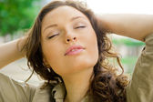 Portrait of a sexy young femalewith closed eyes smiling and breathing fresh air at morning in a park - Outdoor — Stock Photo