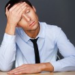 Bored businesspeople: man sitting at desk holding his head. Youn — Stock Photo