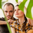 Stock Photo: Attractive young adult couple sitting close on hardwood floor in