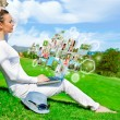 Stock Photo: Pretty woman sitting by tree with laptop computer