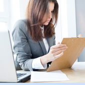 Beautiful business woman looking at papers she holding in her ar — Stock Photo