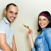 Happy young couple painting their house — Stock Photo