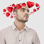 Young man thinking about love. Red hearts are flying around his — Stock Photo