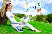Pretty woman sitting by tree with laptop computer — Stock Photo