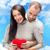 Happy young adult couple with red heart on romantic background w — Stock Photo