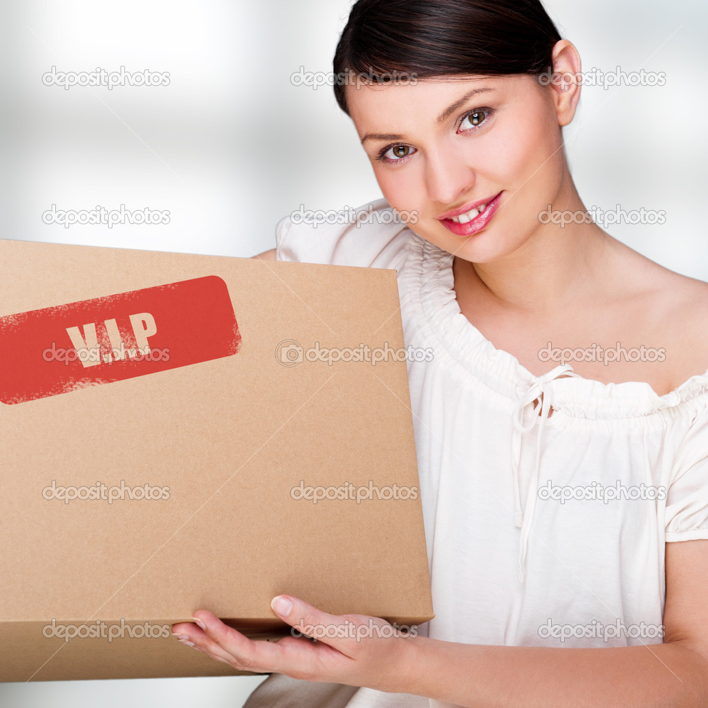 A woman holding a box inside office building or home interior. Package sign on box — Stock Photo #10596368