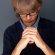 Young man praying against grey background — Stock Photo