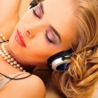 Portrait of gorgeous relaxed young lady listening music smiling — Stock Photo
