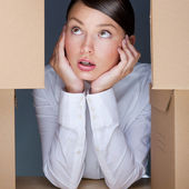 Portrait of young woman surrounded by lots of boxes. Lots of wor — Stock Photo