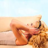 Young Girl enjoys listening music in headphones lying on sofa an — Stock Photo