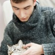 Relaxed man sitting on armchair holding and petting pet cat - Photo