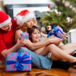 Young happy family near a Christmas tree at home holding gift an — Foto de Stock