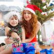 Little girl with her mother sitting together near christmas tree — Stock Photo #8203878