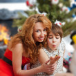 Mother and her daughter sitting together near christmas tree — ストック写真