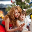Mother and her daughter sitting together near christmas tree — Stockfoto
