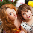Stock Photo: Mother and her daughter sitting together near christmas tree