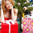 Christmas woman near a Christmas tree holding big gift box while — Foto de Stock