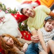 Stockfoto: Happy family embracing and sitting on the floor in front of Chri