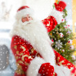Santa sitting at the Christmas tree, near fireplace and looking — Stock Photo #8207772