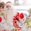 Christmas theme: Santa Claus and little girl having a fun. Indoo - Stock Photo