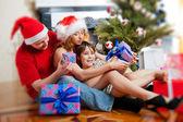 Mladá rodina poblíž vánoční stromeček na domácí hospodářství dárek — Stock fotografie