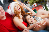Young happy familye near a Christmas tree at home holding gift a — Stock Photo