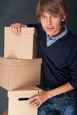 Portrait of young man holding on box against grey wall. He is st — Stock Photo