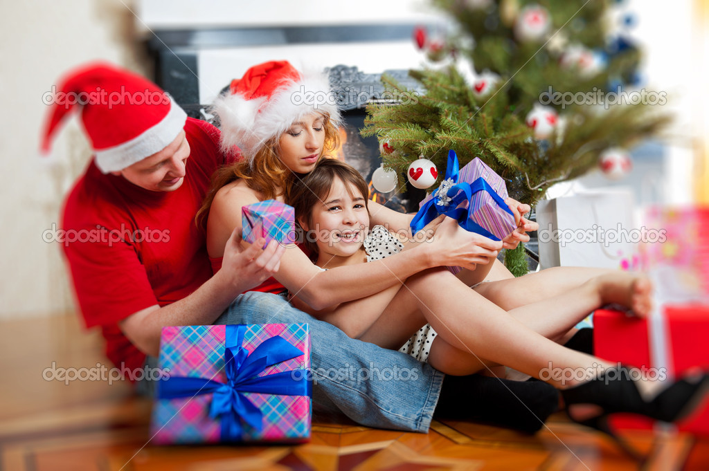 Young happy family near a Christmas tree at home holding gift and warming from fireplace — Stock Photo #8202951