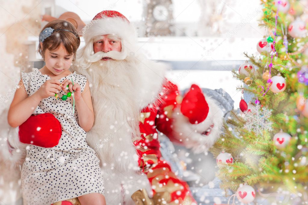 Christmas theme: Santa Claus and little girl having a fun. Indoors at home near christmas tree. — Stock fotografie #8208189